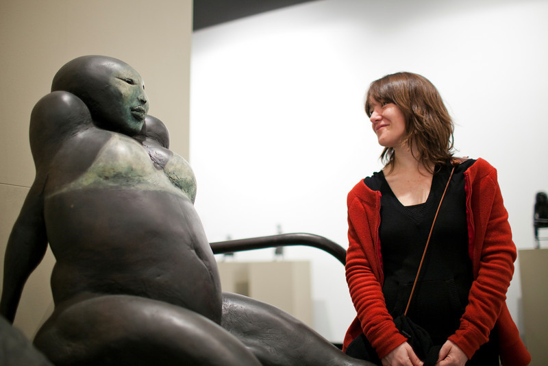 Girl looking at a bronze sculpture by the Dutch artist Cornelis Zitman (born in 1926), exhibited in Santa Ines gallery, Seville, Andalusia, Spain