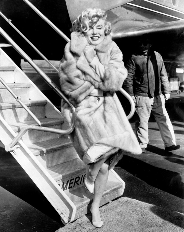 ". American actress Marilyn Monroe poses in 1959 for the photographers at La Guardia Airport before to fly to Chicago, for the presentation of her film ""Some like it hot\"". (STR/AFP/Getty Images)"