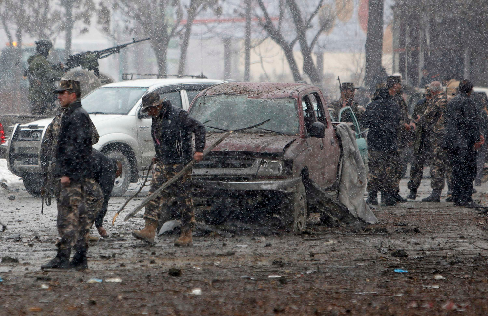 Description of . Afghan security forces investigate at the site of a car bomb attack in Kabul January 16, 2013. Six suicide bombers launched a coordinated attack on Afghanistan's spy agency in Kabul on Wednesday, killing at least two and wounding 22 others, Afghan officials said.  REUTERS/Mohammad Ismail