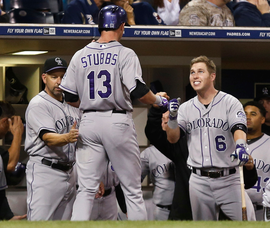 . Colorado Rockies\' Drew Stubbs is greeted by manager Walt Weiss, left, and Corey Dickerson after his solo home run against the San Diego Padres in the eighth inning of a baseball game Tuesday, Sept. 23, 2014, in San Diego.  (AP Photo/Lenny Ignelzi)