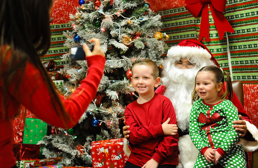 . Five-year-old Noah Tipton and his sister Emma, 3, smile as their mother Shayna Tipton snaps a photo of them with Santa Claus during the annual Santa Pajama Party at the San Bernardino County Museum in Redlands on Friday, Dec. 6, 2013. (Photo by Rachel Luna / Redlands Daily Facts)