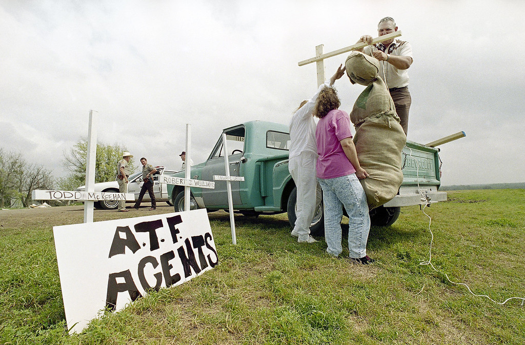 . A trio of anti-ATF demonstrators put up an effigy of Alcohol, Tobacco and Firearms Director Stephan Higgins near the Branch Davidian cult compound near Waco, Texas on Monday, March 29, 1993. Georgia Jenkins, left, of Tulsa, Okla., Billy Walker (in back of truck) and his wife Mary hang the effigy of Higgins. Crosses left depict the ATF officers who died in the raid on the compound on February 28. (AP Photo/Dave Martin)