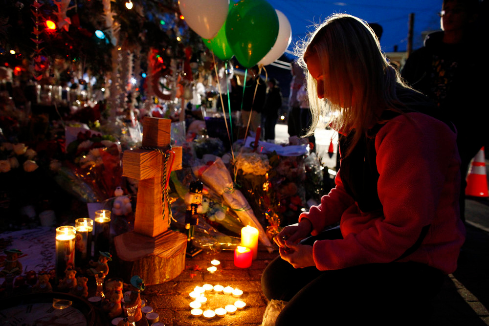 Description of . A girl lights candles at a makeshift memorial for victims of the deadly December 14 shooting at Sandy Hook Elementary school in Newtown, Connecticut, December 20, 2012. Even as they buried more victims of the second-deadliest school shooting in U.S. history on Thursday, residents of Newtown, Connecticut, looked for ways to pressure national leaders to restrict access to weapons. REUTERS/Eric Thayer