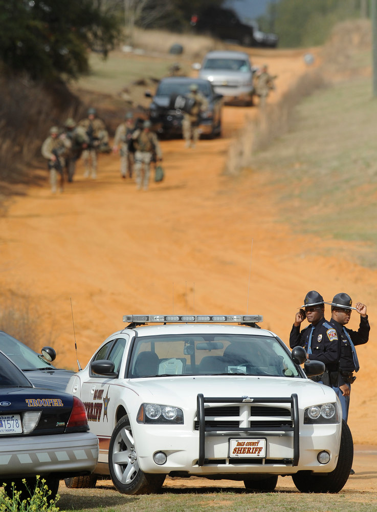 Description of . Police SWAT teams and hostage negotiators are gathered at standoff and hostage scene in Dale County near Ozark, Ala. on Wednesday Jan. 30, 2013. Authorities were locked in a standoff Wednesday with a gunman authorities say on Tuesday intercepted a school bus, killed the driver, snatched a 6-year-old boy and retreated into a bunker at his home in Alabama. (AP Photo/Montgomery Advertiser, Mickey Welsh)