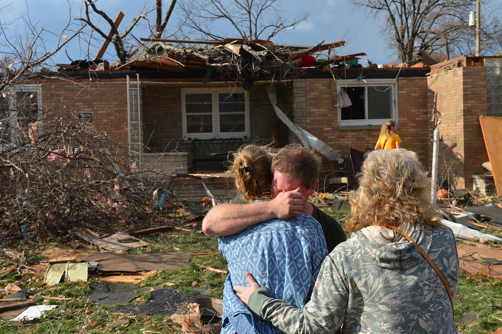 . Ray Baughman embraces family shortly after his home was destroyed by a tornado that left a path of devastation through the north end of Pekin, Il., Sunday, Nov. 17, 2013. Intense thunderstorms and tornadoes swept across the Midwest on Sunday, causing extensive damage in several central Illinois communities while sending people to their basements for shelter. (AP Photo/Journal Star, Fred Zwicky)
