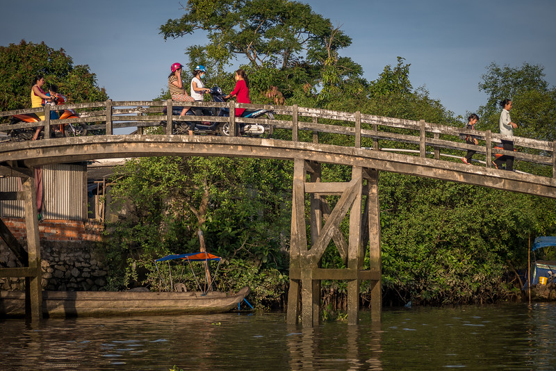 Morning traffic on a wooden bridge over a tributary to the Cổ Chiên River.