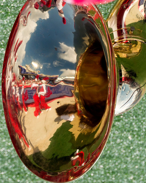 Bandsmen reflected in a tuba bell