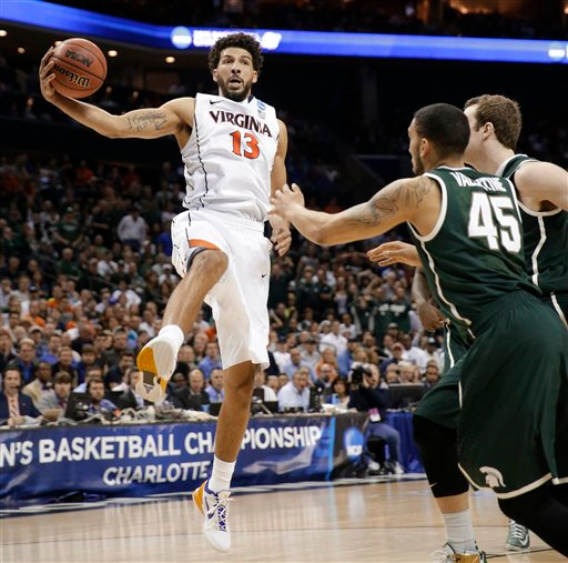 . Virginia\'s Anthony Gill (13) drives against Michigan State\'s Denzel Valentine (45) during the second half of an NCAA tournament college basketball game in the Round of 32 in Charlotte, N.C., Sunday, March 22, 2015. (AP Photo/Gerald Herbert)