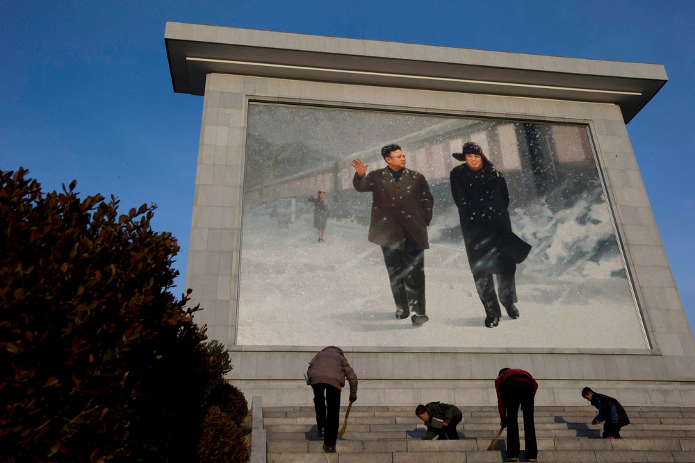 . North Korean children sweep the steps near a giant mosaic of late North Korean leaders Kim Il Sung, right, and Kim Jong Il in Pyongyang, North Korea, Wednesday, Dec. 19, 2012. (AP Photo/Ng Han Guan)