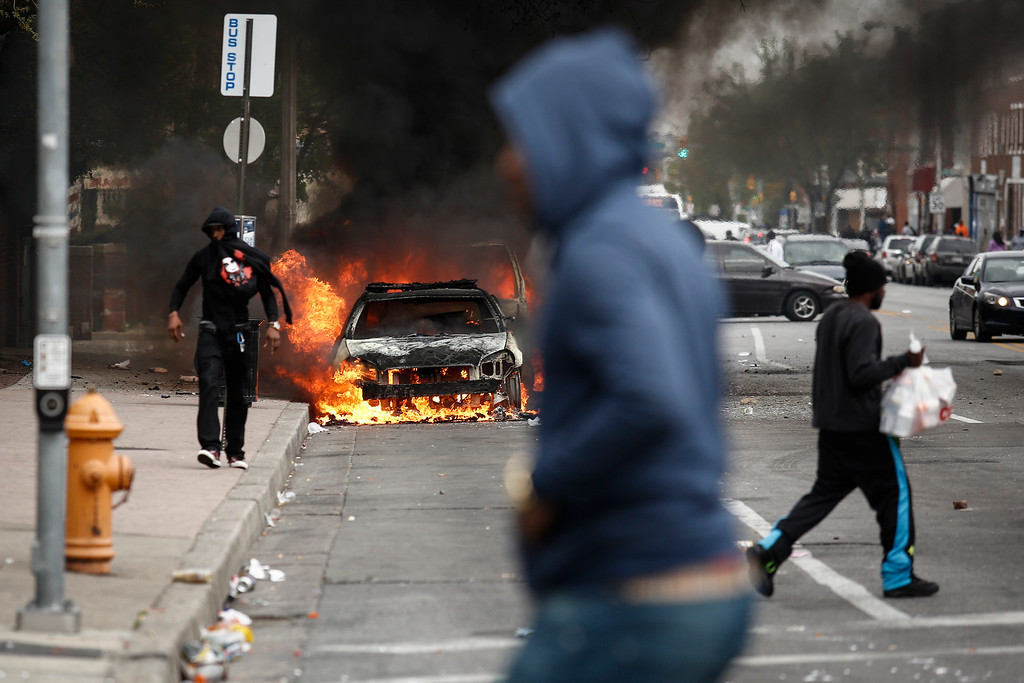 . BALTIMORE, MD - APRIL 27:  People walk past burning cars near the intersection of Pennsylvania Avenue and North Avenue, April 27, 2015 in Baltimore, Maryland. Riots have erupted in Baltimore following the funeral service for Freddie Gray, who died last week while in Baltimore Police custody. (Photo by Drew Angerer/Getty Images)