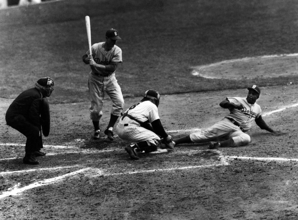 . Brooklyn Dodgers\' Jackie Robinson safely steals home plate under the tag attempt of Yankees catcher Yogi Berra in the eighth inning of the World Series opener in this Sept. 28, 1955 photo in New York\'s Yankee Stadium.   Robinson was voted 29th of the top 100 athletes of the century by a selected panel assembled by The Associated Press. (AP Photo/John Rooney)