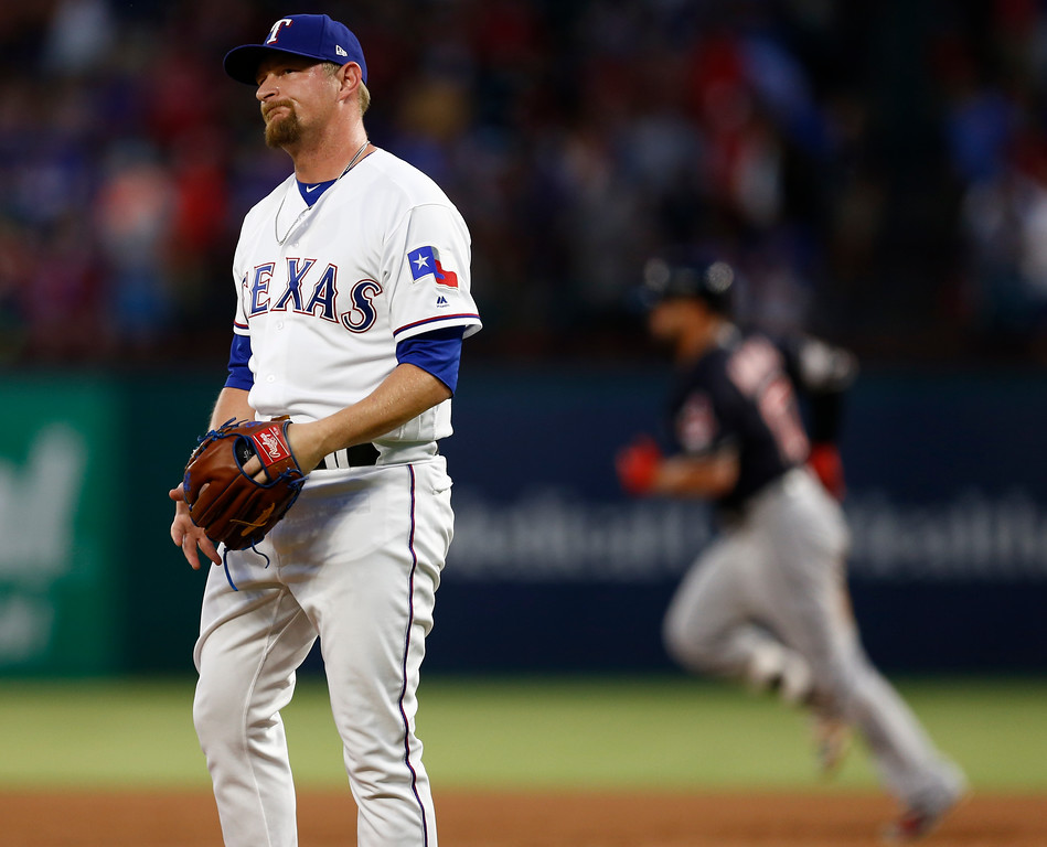 . Texas Rangers relief pitcher Austin Bibens-Dirkx reacts after giving up a two-run home run to Cleveland Indians\' Yonder Alonso, background, during the fifth inning of a baseball game, Saturday, July 21, 2018, in Arlington, Texas. (AP Photo/Jim Cowsert)