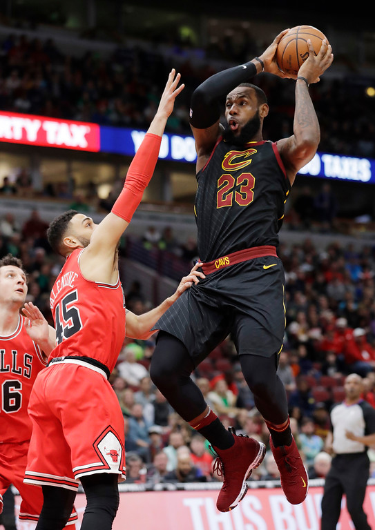 . Cleveland Cavaliers forward LeBron James, right, drives to the basket against Chicago Bulls guard Denzel Valentine, center, and forward Paul Zipser during the first half of an NBA basketball game Saturday, March 17, 2018, in Chicago. (AP Photo/Nam Y. Huh)