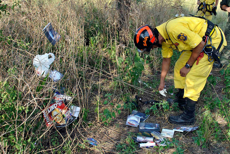 . A rescue worker inspects campaign materials of Paraguayan presidential candidate for the UNASE party Lino Oviedo that were scattered near the site where a helicopter carrying Oviedo crashed in Presidente Hayes province February 3, 2013. Oviedo, who led a 1989 coup that overthrew dictator Alfredo Stroessner, died in a helicopter crash over the weekend. Police rescuers found his body on Sunday in the wreckage of a helicopter crash in northern Paraguay where he was traveling for a campaign event. He was 69. REUTERS/Roque Gonzalez/ABC Color
