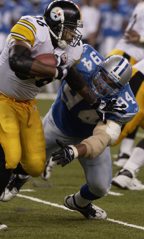 . Steelers running back Jerome Bettis (left) shoves Lions\' tackle Luther Elliss out of the way as he picks up some yardage during the Detroit Lions 34-22 loss to the Pittsburgh Steelers at Ford Field Sat. Aug. 24, 2002.