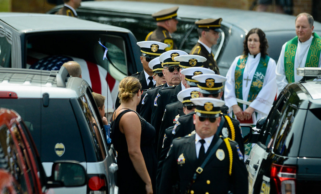 . The honor guard exits after placing the casket of officer Patrick in the hearse for the processional to the cemetery.  (Pioneer Press: Ben Garvin)