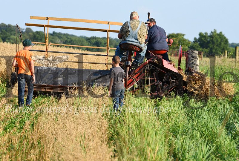 Harold Aughton/Butler Eagle: Terry Foertsch (left), his dad, Vernon and children, Timothy, 11, and Granite, 15, of Saxonburg recently cut about 1 1/2 acres of oats with an old-fashion grain binder on Guy Daubenspeck's farm in Connoquennessing Twp. The Foertsch family and others will be separating the staw and chaff from the grain using a threshing machine at this year's farm show.