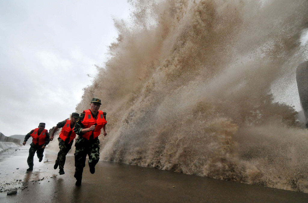 . A huge wave hits the dike as guards run along it as Typhoon Fitow moves to make its landfall in Wenling, east China\'s Zhejiang province on October 6, 2013.  China was on its highest alert for Typhoon Fitow on October 6, with tens of thousands evacuated as the storm was set to slam into the east coast.  STR/AFP/Getty Images