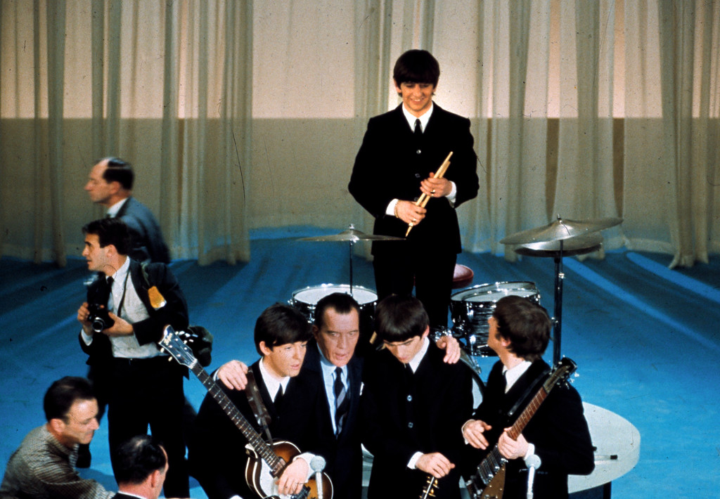 . The British rock and roll group the Beatles are shown on stage with Ed Sullivan before their live television appearance on the The Ed Sullivan Show at CBS\' Studio 50 in New York City, Feb. 9, 1964.  From left are, Paul McCartney, Sullivan, George Harrison, Ringo Starr, standing, and John Lennon.  (AP Photo)