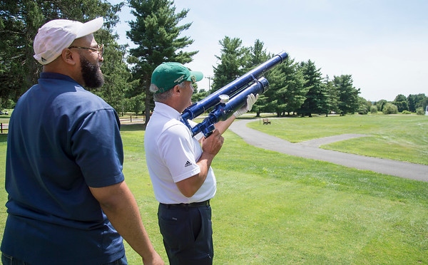 08/05/19 Wesley Bunnell | Staff David Onofrio from Torrington Savings Bank takes his turn using a golf cannon which launches golf balls with aerodynamic fins attached for a closest to the target contest as Gil Bransford from CT Golf Event Planner helps. The Bristol Chamber of Commerce held their annual golf tournament on Monday at Tunxis Country Club in Farmington.
