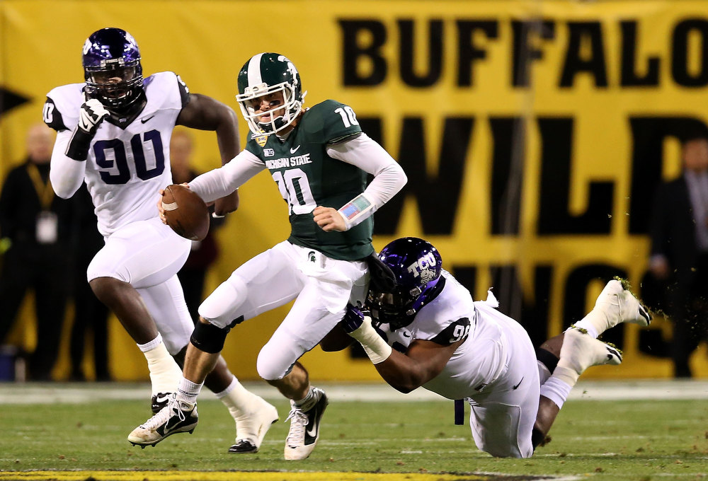 Description of . Quarterback Andrew Maxwell #10 of the Michigan State Spartans is sacked by defensive tackle Chucky Hunter #96 of the TCU Horned Frogs during the Buffalo Wild Wings Bowl at Sun Devil Stadium on December 29, 2012 in Tempe, Arizona.  (Photo by Christian Petersen/Getty Images)