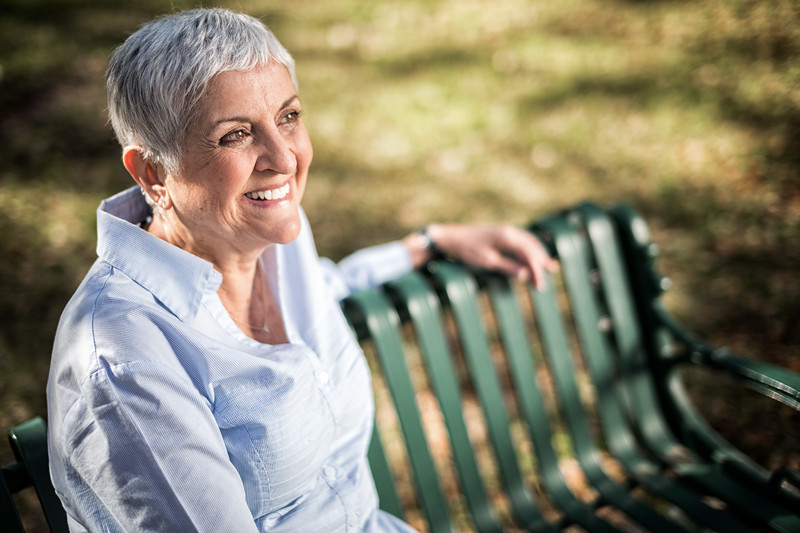 A woman sitting on a park bench smiling proudly.