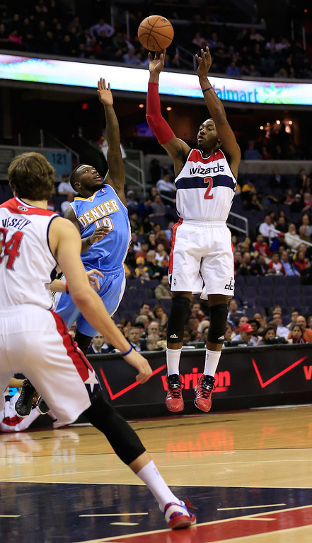 . John Wall #2 of the Washington Wizards puts up a shot in front of Nate Robinson #10 of the Denver Nuggets during the first half at Verizon Center on December 9, 2013 in Washington, DC.    (Photo by Rob Carr/Getty Images)