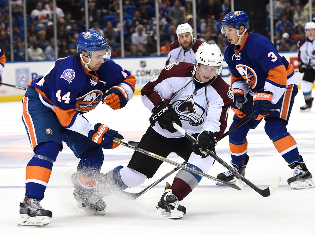 . New York Islanders defenseman Calvin de Haan (44) and Colorado Avalanche center Matt Duchene (9) battle for the puck in the third period of an NHL hockey game at Nassau Coliseum on Tuesday, Nov. 11, 2014, in Uniondale, N.Y. The Islanders won 6-0. (AP Photo/Kathy Kmonicek)