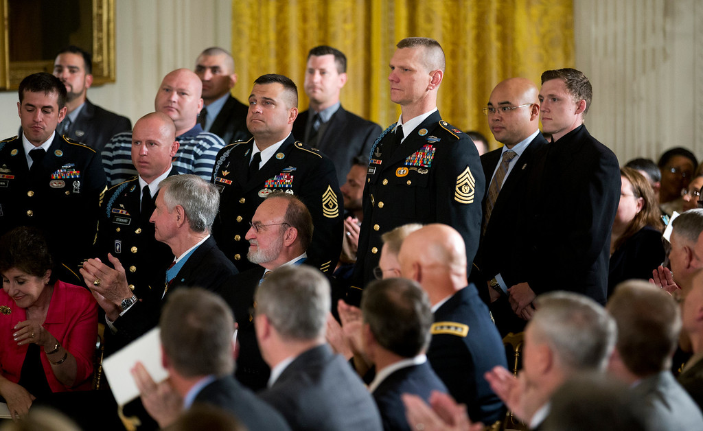 . Former Army Spc. Kain Schilling, standing right, the soldier that former Army Sgt. Kyle J. White saved, and members of the second battalion, Chosen Company of the 173rd Airborne Brigade, stand at attention as they were recognized by President Barack Obama, and applauded by the invited guests during a ceremony awarding the Medal of Honor to former Army Sgt. Kyle J. White, Tuesday, May 13, 2014, in the East Room of the White House in Washington.  (AP Photo)