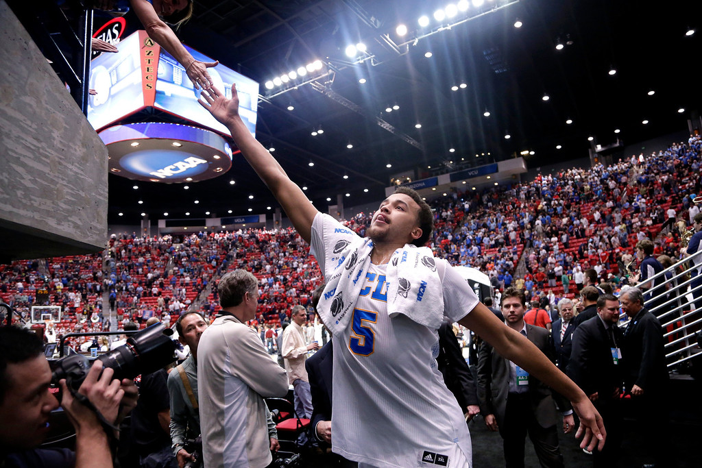 . UCLA forward Kyle Anderson (5) touches hands with a fan after defeating Stephen F. Austin in a  third-round game of the NCAA college basketball tournament, Sunday, March 23, 2014, in San Diego. UCLA won 77-60. (AP Photo/Gregory Bull)