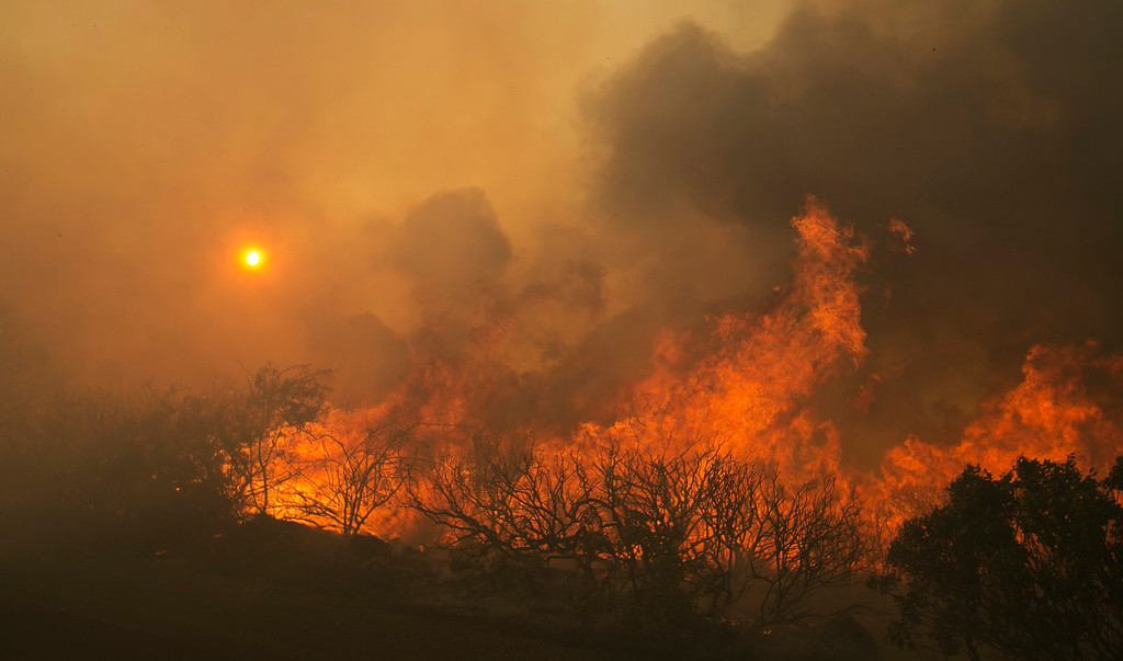 . The sun rises as flames from a wildfire burn Monday, Oct. 9, 2017, east of Napa, Calif. The fire is one of several burning across Northern California\'s wine country. (AP Photo/Rich Pedroncelli)