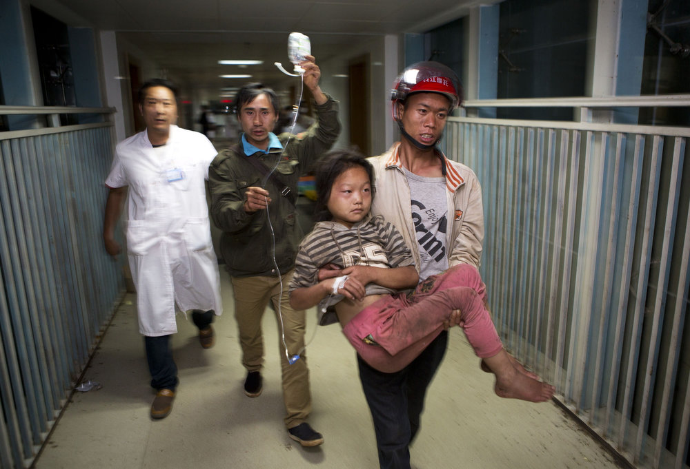 . This picture taken on August 3, 2014 shows a man (R) carrying an injured girl in a hospital during the first night after a 6.1 magnitude earthquake hit Ludian county in Zhaotong, in southwest China\'s Yunnan province.  More than 367 people died and nearly 2,000 were injured when a strong earthquake hit southwest China\'s mountainous Yunnan province on August 3, bringing homes crashing to the ground and sparking a massive relief operation.     STR/AFP/Getty Images