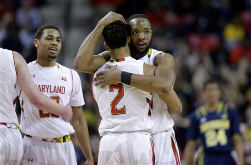 . Maryland guard/forward Dez Wells, right, hugs teammate Melo Trimble in the final moments of an NCAA college basketball game against Michigan, Saturday, Feb. 28, 2015, in College Park, Md. (AP Photo/Patrick Semansky)