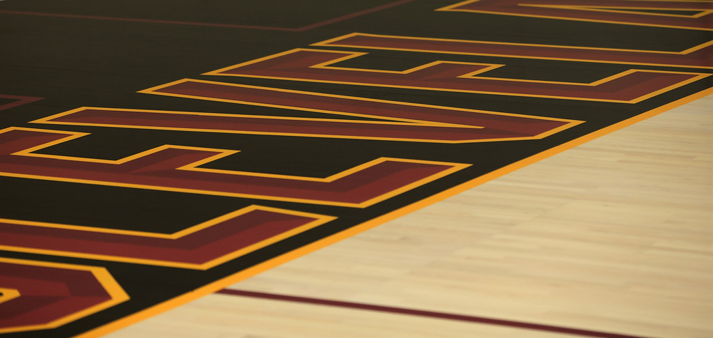 . The maple hardwood floor features a light stain throughout the entire court and is framed with a bold black perimeter. Black was officially introduced as a new and permanent addition to the Cavaliers color palette as part of the team�s updated brand. The color black is a nod to the historic turning point in the 2016 NBA Finals when the Cavs wore their black-sleeved uniforms in Games 5 and 7 of the NBA Finals on their way to winning the NBA Championship. The lane is solid wine with bright gold accents. (Courtesy Cleveland Cavaliers)