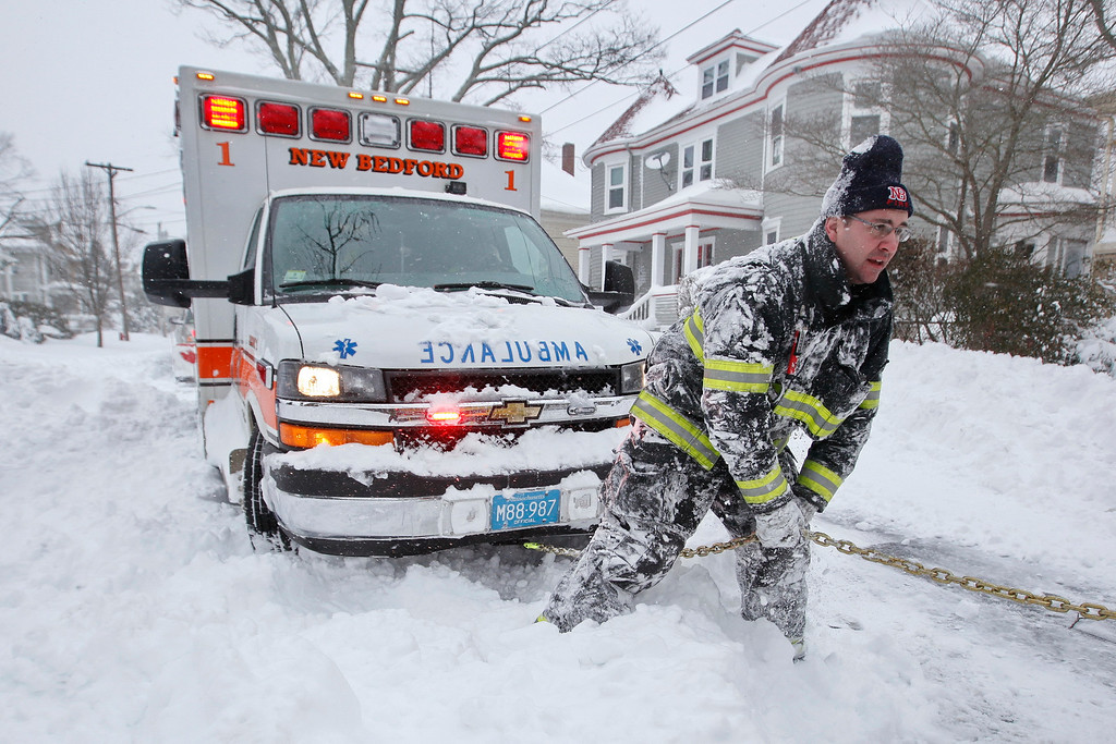 . New Bedford firefighter Lt. Eric Hartford tries to dig out an ambulance carrying a patient en route to St. Lukes Hospital in New Bedford, Mass., on Tuesday, Jan. 27, 2015, as the region digs itself out of the snow storm that covered the area. The nor\'easter was predicted to continue to pound Connecticut, Rhode Island, Massachusetts, New Hampshire and Maine with snow and wind through Tuesday. Total accumulation was expected to reach or exceed two feet in most of Massachusetts, potentially making it one of the top snowstorms of all time. (AP Photo/The Standard-Times, Peter Pereira)