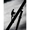 Man climbing a crane as the fair is put up - One of a set of Street Photography images by Stephen Ignacio