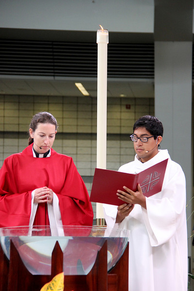 The Rev. Erin Evans and the Rev. David Rojas Martinez invite all to worship at the baptismal font.