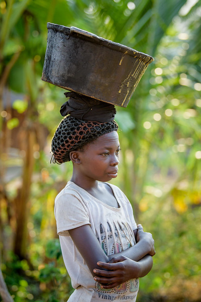 """Each day Marie Ngalula, 14 yr-old girl, makes the difficult journey to collect water, carrying a heavy cast iron pot down a steep embankment. SOmetimes she also sells water to others, to earn money for her family in Tubuluku, Kananga, DRC.  Marie lives with her father, Alexandre Tshimanga, her mother, Ntumba Kalombo Antoinette and her brothers and sisters: 1-Kena Tshimanga, 12 2-Kankonde Moise, 10 3-Munamba Angel, 8 4-Musungayi Andre, 6 5-Mubuyi Tshimanga, 4  Marie lives in a small village outside of Kananga, Democratic Republic of Congo, DRC, called Tubuluku, which means antelopes (plural). Her house is a two-room hut with a thatched roof.  Handful of wooden chairs are the only furniture. She lives here with an extended family of 13.  Home Life Marie is a bright girl but there is a sadness in her eyes. Marie's mother is in the nearby health clinic with a staph infection that has caused a huge abscess on her right side. It has become very serious. As a result, Marie has assumed many of the household duties.  She's forced, at 14, to assume the duties of an adult. Besides cooking for her brothers and sisters, she sweeps up the husks from palm nuts she crushes. She saves the husks to use as kindling for the fire. Marie and her siblings all sleep together in one room, huddled together for warmth and cover by an old and torn mosquito net.  School Marie's father laments his inability to send her back to school. """"Marie is intelligent,"""" he says. """"She could help me very much someday.  I'd like to send her back to school but I can't afford it. I'd like if she could further her studies even as far as university so that she can help me take care of her brothers and sisters someday.""""  Marie and her friends often play on the grass in front of the school they can't afford to go to.  Hunger Marie's family is desperately hungry in the days we visit them. Because her mother is sick and his father spends his days tending to her in the clinic, there is no money for food. Because there """