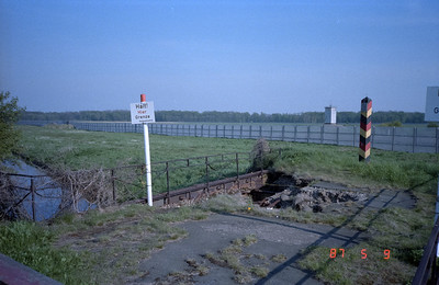 A destroyed railway bridge leading to the border with the DDR.  The white building on the DDR side houses ever vigilant border guards.  These guard buildings, and those of other designs, are situated all along the entire DDR border, guarding the entire 'NO-Go' strip separating the two sides.