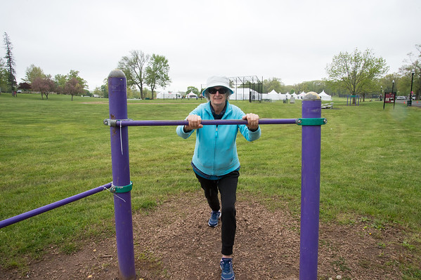 05/10/19 Wesley Bunnell | Staff Wanda Wojtkielewicz stretches on a piece of exercise equipment at Walnut Hill Park on Friday afternoon as tents for the CT Breast Health Initiative Race in the Park are set up in the background. Wanda walks 6 miles every day around the park in addition to practicing yoga.