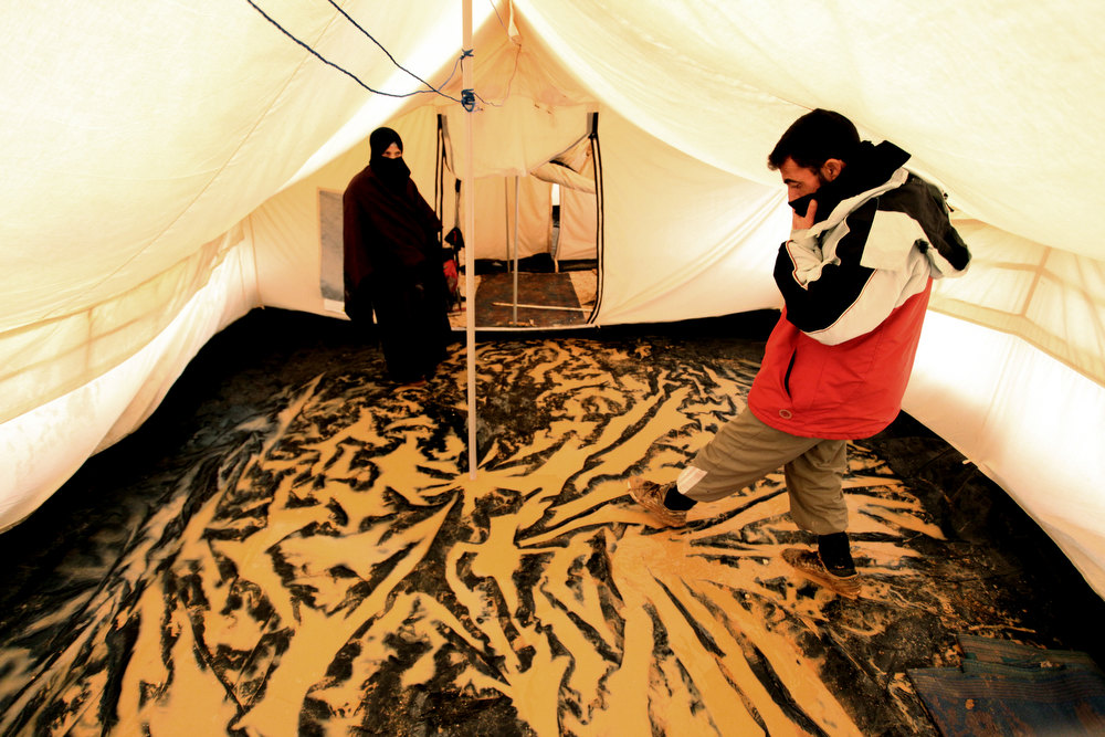 Description of . Syrian refugees stand inside their tent after a flooded hit Zaatari Syrian refugee camp, near the Syrian border in Mafraq, Jordan, Tuesday, Jan. 8, 2013. Syrian refugees in a Jordanian camp attacked aid workers with sticks and stones on Tuesday, frustrated after cold, howling winds swept away their tents and torrential rains flooded muddy streets overnight. Police said seven aid workers were injured. (AP Photo/Mohammad Hannon)