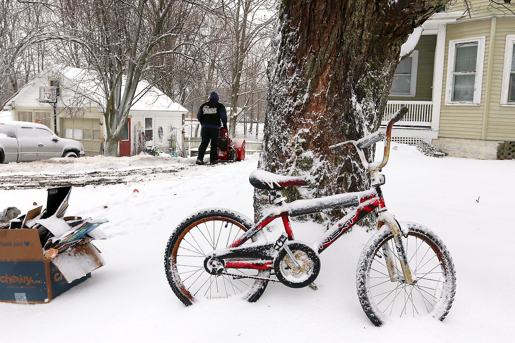 . A bike sits in this yard on Davis Road in Shirley as the owner of the house Bill Clapper blows his driveway in the background. SENTINEL & ENTERPRISE/JOHN LOVE