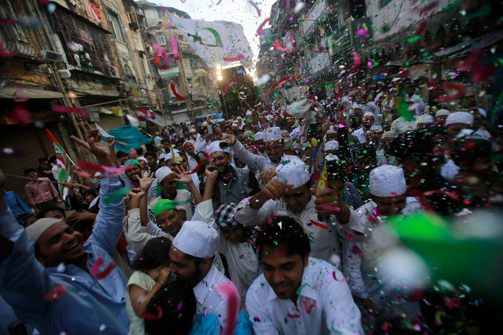 . Confetti falls on Indian Muslims walking in a procession of devotees on Eid-e-Milad marking the birth anniversary of the Prophet Muhammad, in Mumbai, India, Tuesday, Jan. 14, 2014. Some thousands of people gather along the streets to chant religious slogans during the annual Eid-e-Milad festival marking the anniversary of Prophet Muhammad\'s birth.  (AP Photo/Rafiq Maqbool)