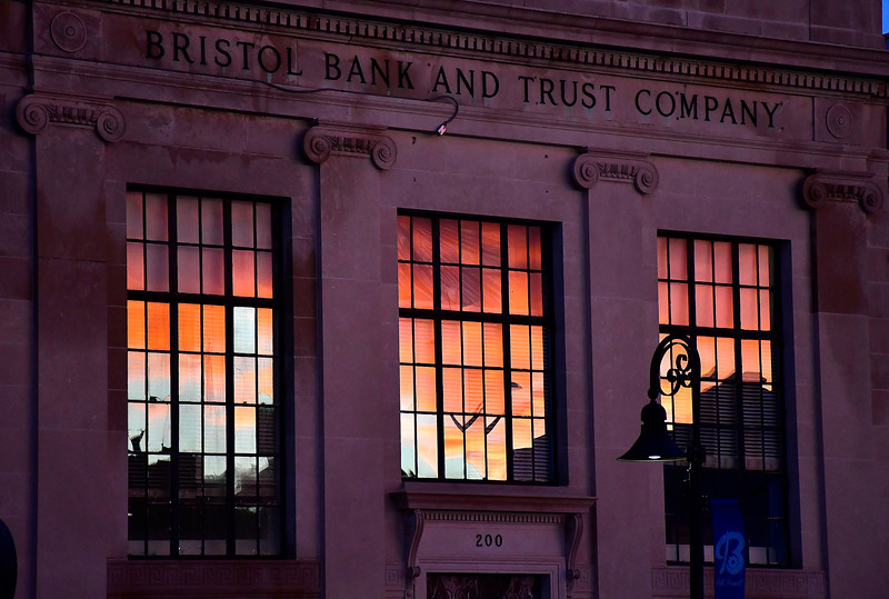 1/10/2019 Mike Orazzi | Staff The sunset as seen in a reflection on the form Bristol Bank and Truck Company building on Main Street in downtown Bristol Thursday.