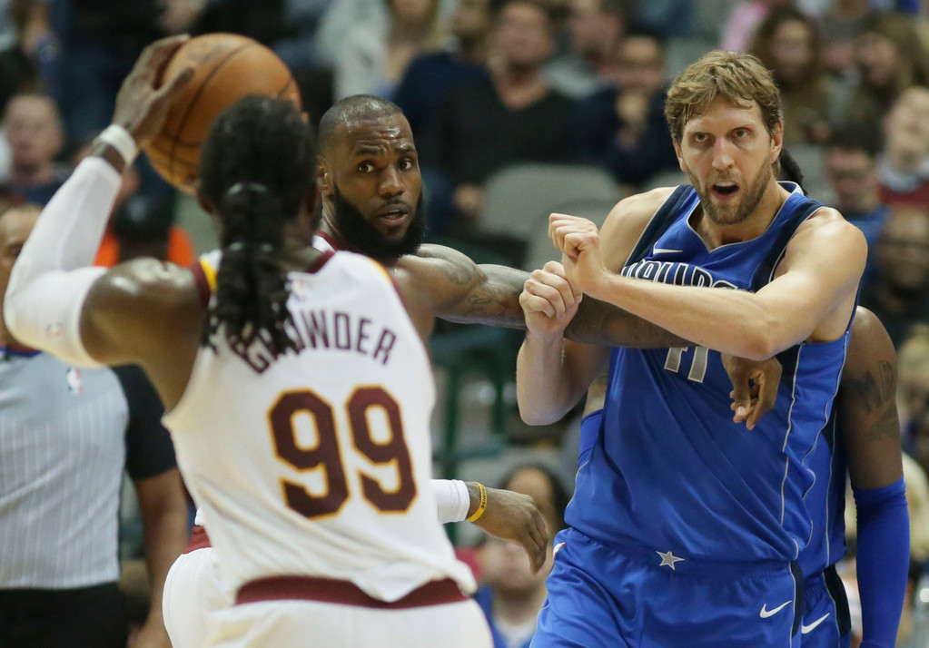 . Cleveland Cavaliers forward LeBron James (23) ties up Dallas Mavericks forward Dirk Nowitzki (41), of Germany, as Cavaliers Jae Crowder (99) shoots during the second half of an NBA basketball game in Dallas, Saturday, Nov. 11, 2017. (AP Photo/LM Otero)