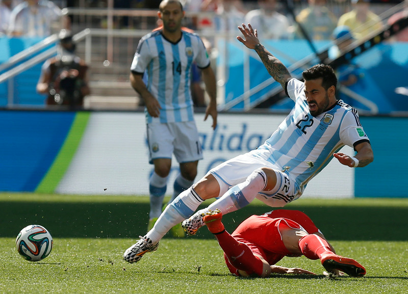 . Argentina\'s Ezequiel Lavezzi, top, is challenged by Switzerland\'s Xherdan Shaqiri during the World Cup round of 16 soccer match between Argentina and Switzerland at the Itaquerao Stadium in Sao Paulo, Brazil, Tuesday, July 1, 2014. (AP Photo/Frank Augstein)