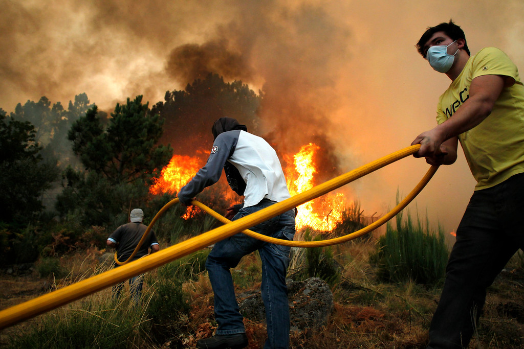 . Inhabitants use a hose in an effort to fight a wildfire near Caramulo, north Portugal, Thursday, Aug. 29, 2013.  (AP Photo/Francisco Seco)