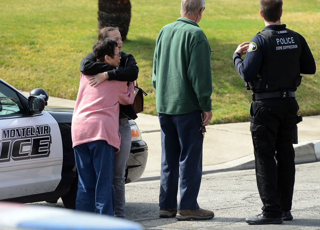 . Shelby De Graff, of Montclair, hugs her grandmother Noreen, of Big Bear Lake, as CHP, Fontana and Montclair Police officials investigate the scene where a man, wanted for grand theft auto, tried to break into De Graff\'s home in the 5500 block of Deodar Street in Montclair, CA., Wednesday, February 19, 2014. The suspect crashed the 18-wheeler on the westbound 10 freeway before running into the nearby neighborhood where he was tackled by Shelby De Graff while trying to break into her home as police arrived. (Photo by Jennifer Cappuccio Maher/Inland Valley Daily Bulletin)