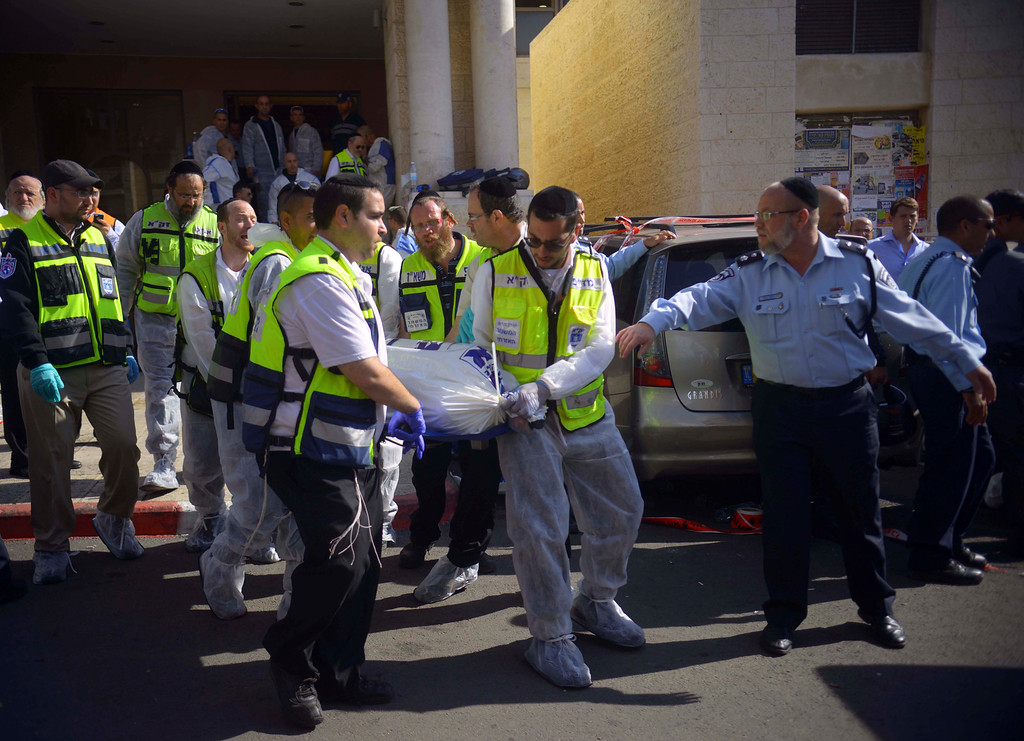. Paramedics carry a body out of a synagogue after an attack in Har Nof, an ultra-Orthodox neighborhood on the western edge of Jerusalem, Tuesday, Nov. 18, 2014. Two Palestinian cousins stormed the Jerusalem synagogue attacking worshippers with meat cleavers and a gun during morning prayers and killing four people in the cityís bloodiest attack in years. The attackers were killed in a shootout with police. (AP Photo/Mahmoud Illean)