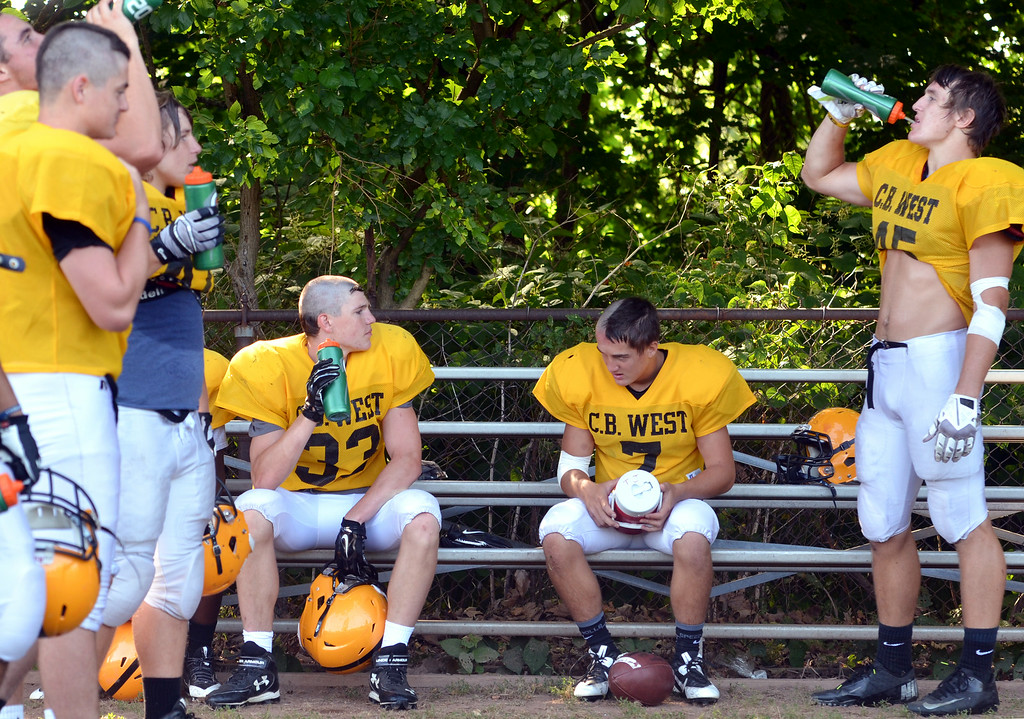 . Central Bucks West football players take a short break at a morning practice.    Tuesday,  August 19, 2014.   Photo by Geoff Patton